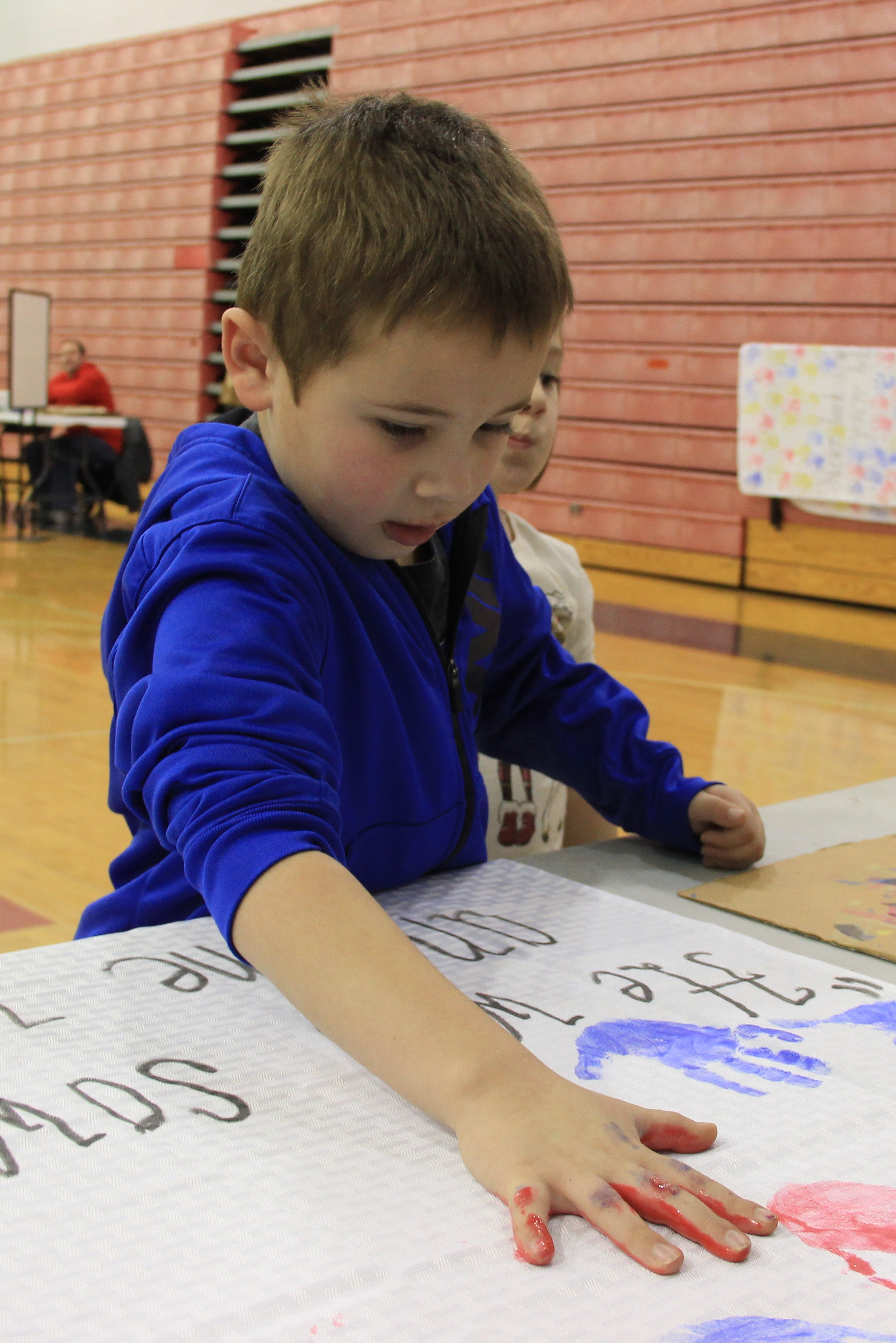 MSE student decorates a table cloth with his hand print.