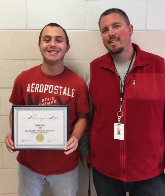 Thomas Nye accepting his certificate from Mr. Brandon Richards for being selected as a participant in the Student Traveling Art Exhibit.