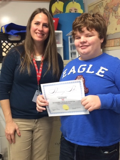 Jacob Martin accepting his certificate from Ms. Anita McNeal for being selected as a participant in the Student Traveling Art Exhibit.
