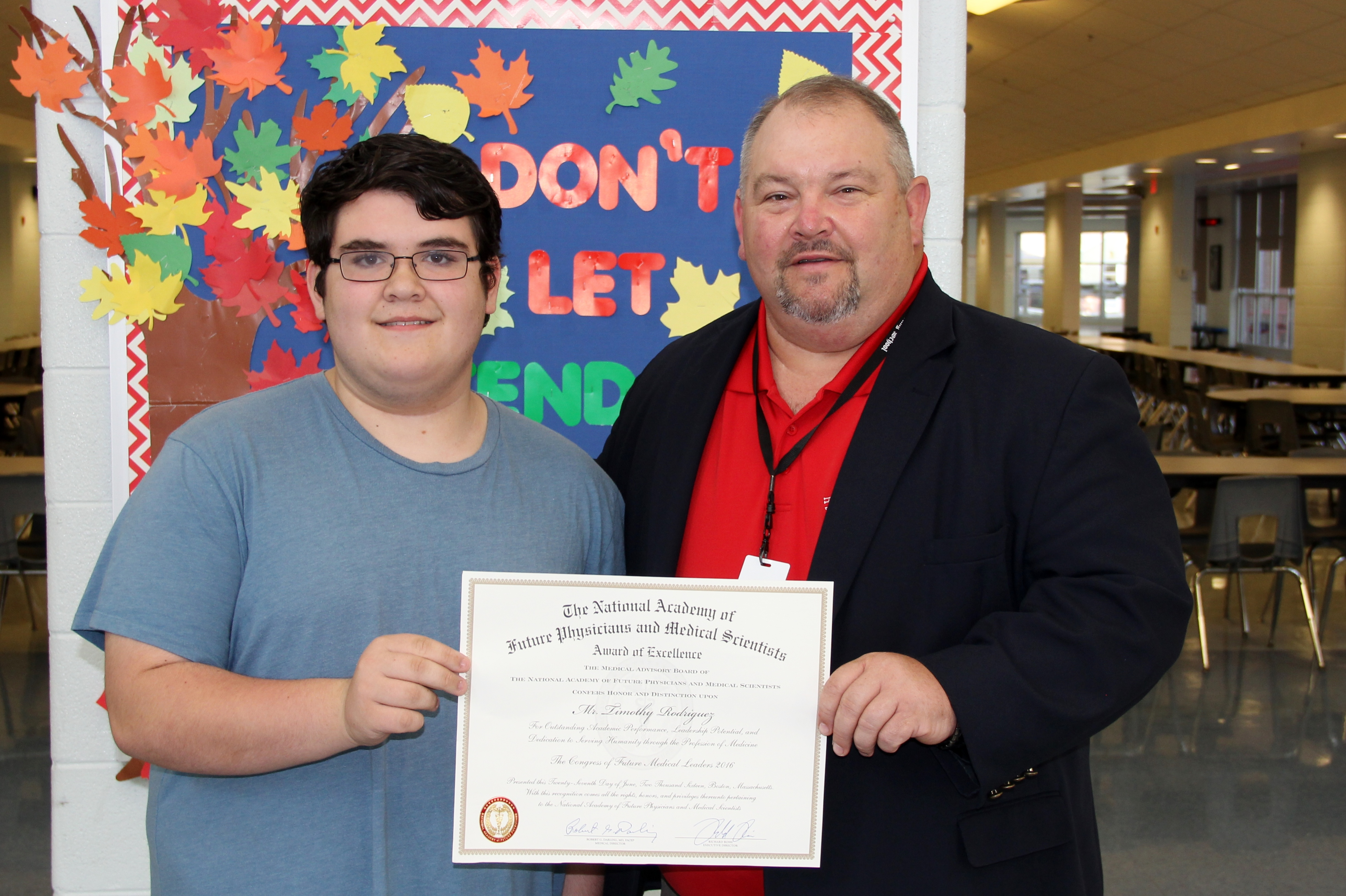 Student Timothy Rodriguez and Principal Rocky Franz pose with Timothy's certificate